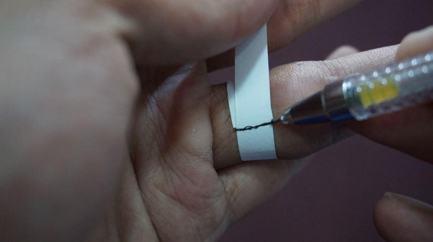 menandai batas kertas dengan pulpen